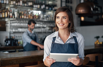 Buy stock photo Cropped shot of an attractive young woman working on a digital tablet while standing in her coffee shop