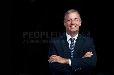 Buy stock photo Studio shot of a mature businessman posing against a dark background