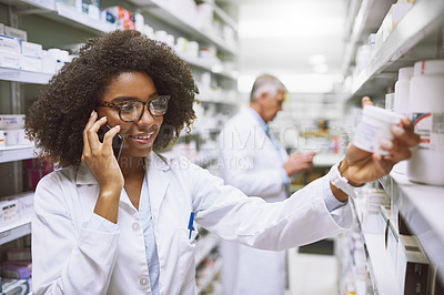 Buy stock photo Shot of a cheerful young female pharmacist talking on her cellphone while reading the back of a medication box