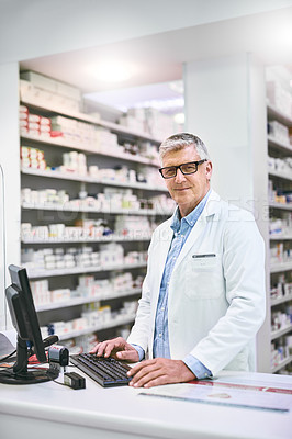 Buy stock photo Portrait of a confident mature male pharmacist typing on a computer while looking at the camera in the pharmacy