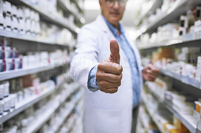 Buy stock photo Shot of a unrecognizable mature male pharmacist showing thumbs of to the camera with a closeup on his hand