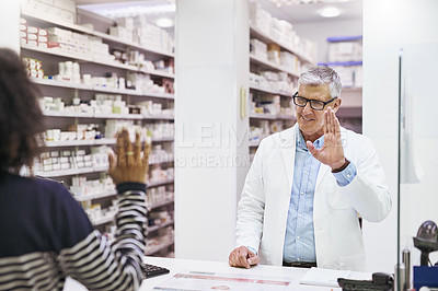 Buy stock photo Shot of a cheerful mature male pharmacist greeting a customer inside of the pharmacy