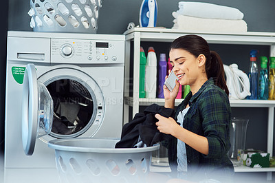 Buy stock photo Cropped shot of an attractive young woman using her cellphone while doing laundry at home