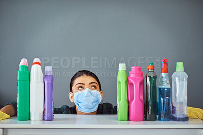 Buy stock photo Studio shot of an attractive young woman wearing a mask while surrounded by cleaning products