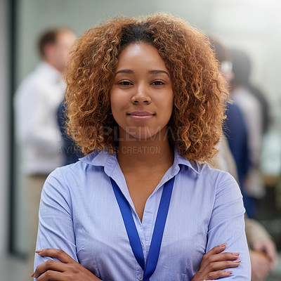 Buy stock photo Portrait of a young woman standing in an office with colleagues in the background