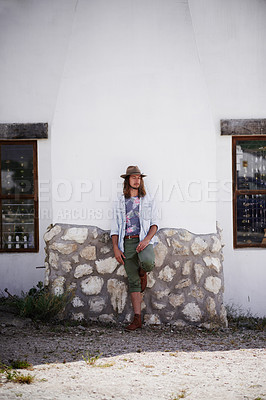 Buy stock photo Shot of a trendy young man leaning against the wall of a building outside