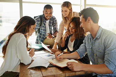 Buy stock photo Shot of a group of students working together on campus