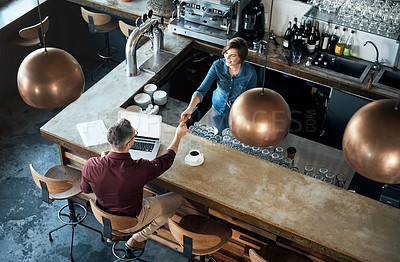 Buy stock photo High angle shot of an attractive female barista taking payment from a male customer