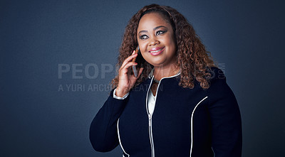 Buy stock photo Studio shot of a cheerful young businesswoman talking on her cellphone to a client while looking in a certain direction
