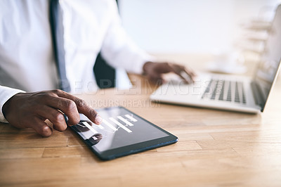 Buy stock photo Shot of  a unrecognizable business person typing on a laptop while using a tablet as well