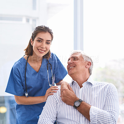 Buy stock photo Portrait of a cheerful young female doctor holding a patient's hand while looking at the camera inside a clinic