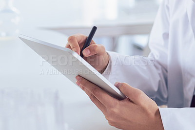 Buy stock photo Cropped shot of a unrecognizable scientist's hands making notes on a digital tablet inside of a laboratory