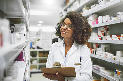 Buy stock photo Shot of a cheerful young female pharmacist checking stock on the shelves of a pharmacy