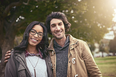 Buy stock photo Portrait of a affectionate young couple holding each other in an embrace while looking at the camera outside in a park