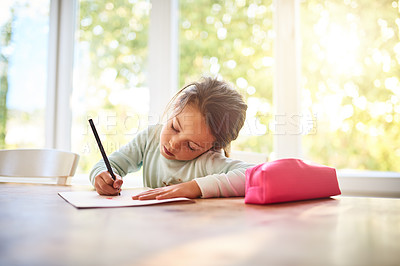 Buy stock photo Shot of a focused little girl drawing pictures in a book while being seated at a table at home