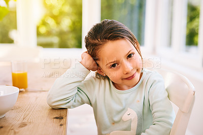 Buy stock photo Portrait of a cheerful little girl sitting next to a kitchen table with her one hand next to her head while looking at the camera