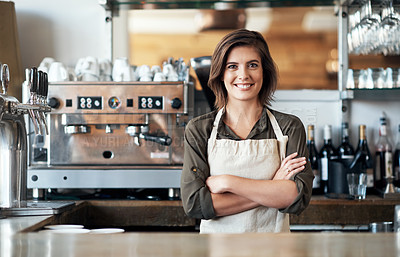 Buy stock photo Portrait of a cheerful female bartender standing behind the bar counter with her arms folded