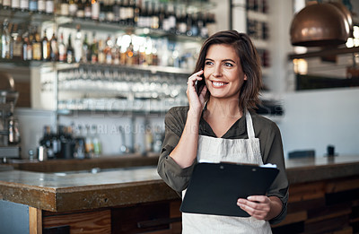 Buy stock photo Shot of a cheerful young female bartender making a call and contemplating while standing inside of a restaurant