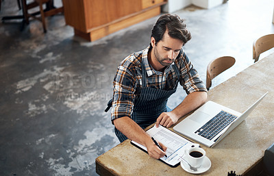 Buy stock photo Shot of a focused young man working on his laptop and making notes while being seated in a restaurant