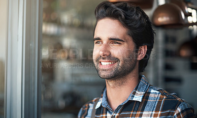 Buy stock photo Shot of a cheerful young man standing and looking in a certain direction inside of a building