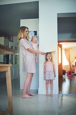 Buy stock photo Shot of a mother carrying her baby and measuring her daughter's height against a wall