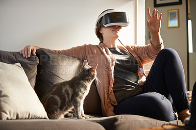 Buy stock photo Shot of a focused unrecognizable young woman having fun with a virtual reality headset while her cat looks at her in confusion at home