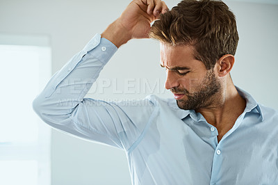 Buy stock photo Shot of a handsome young man smelling his armpits at home
