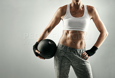 Buy stock photo Studio shot of an unrecognizable young woman working out with a medicine ball against a grey background