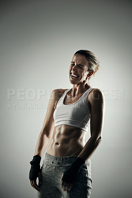 Buy stock photo Studio shot of an athletic young sportswoman laughing while posing against a grey background