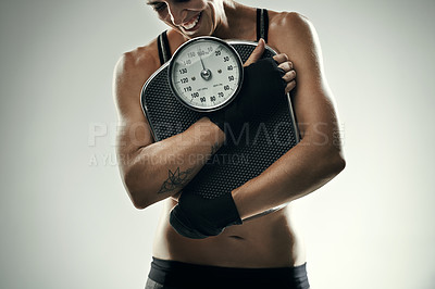 Buy stock photo Studio shot of an unrecognizable young sportswoman clutching a weightscale against a grey background