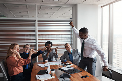 Buy stock photo Shot of a group of businesspeople cheering a colleague in an office