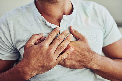 Buy stock photo Shot of a unrecognisable young man holding his chest in discomfort with his hands due to pain in that area