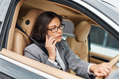 Buy stock photo Shot of a businesswoman talking on her phone while driving her car