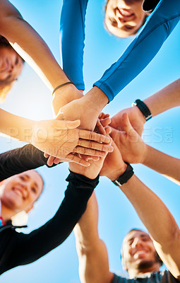 Buy stock photo Low angle shot of a group of young cheerful friends forming a huddle before a fitness exercise outside during the day