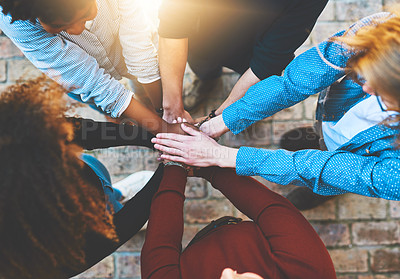 Buy stock photo High angle shot of an unrecognizable group of college friends standing outside with their hands in a huddle