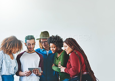 Buy stock photo Studio shot of a group of young people using a digital tablet together