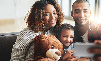 Buy stock photo Shot of an adorable little girl taking selfies with her parents at home on a mobile phone