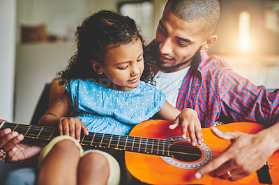 Buy stock photo Shot of an adorable little girl and her father playing a guitar together on the sofa at home