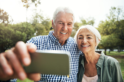 Buy stock photo Shot of a happy senior couple taking selfies together in the park