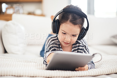 Buy stock photo Shot of an adorable little girl wearing headphones while using a digital tablet at home