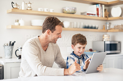 Buy stock photo Cropped shot of a handsome young man and his son using a tablet while sitting in the kitchen
