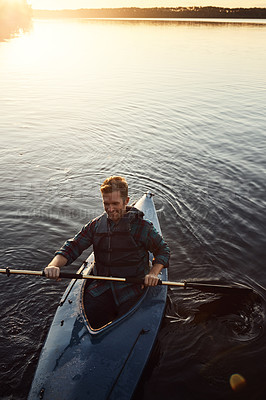 Buy stock photo High angle shot of a young man kayaking on a lake outdoors