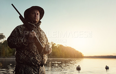Buy stock photo Shot of a young man hunting duck while dressed in camo outdoors