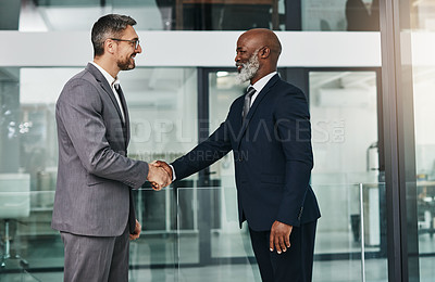 Buy stock photo Shot of two businessmen shaking hands in an modern office