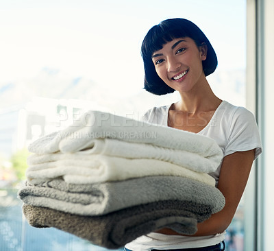 Buy stock photo Cropped shot of a young woman carrying a pile of towels on laundry day at home