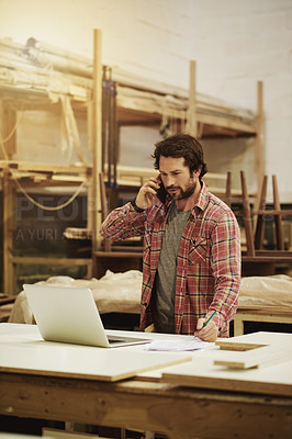 Buy stock photo Shot of a craftsman talking on his cellphone while using his laptop