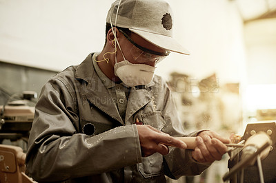 Buy stock photo Cropped shot of a handsome young carpenter chiselling away on a piece of wood in his workshop