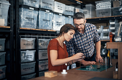 Buy stock photo Shot of a man and woman manufacturing something together in a workshop