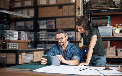 Buy stock photo Shot of two colleagues using a digital tablet in a workshop