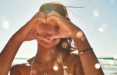 Buy stock photo Portrait of a beautiful young woman making a heart shaped gesture with her hands at the beach